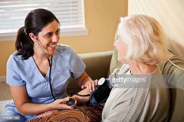 Nurse taking senior woman's blood pressure