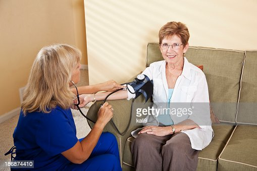 Nurse taking senior woman's blood pressure : Stock Photo