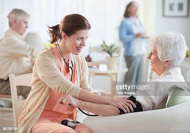 Nurse taking senior womans blood pressure