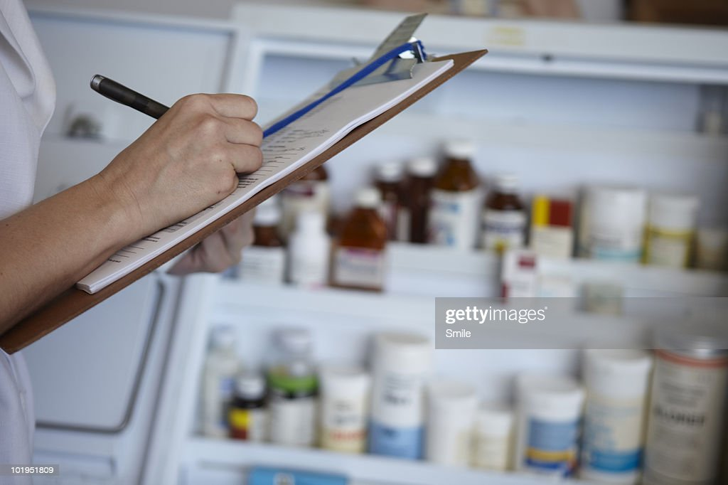 Nurse taking stock of pharmaceutical drugs : Stock Photo