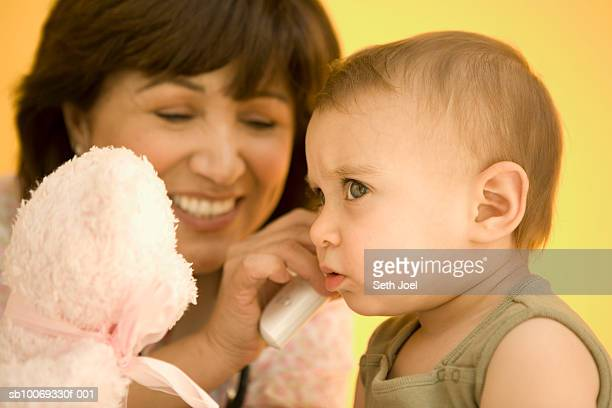 Nurse taking temperature of girl (12-17 months) with ear thermometer, studio shot