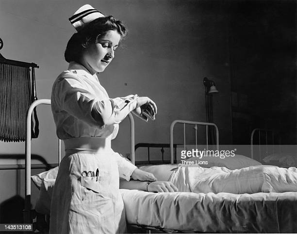 A nurse taking the pulse of a male patient in a US navy hospital in Corpus Christi Texas circa 1955