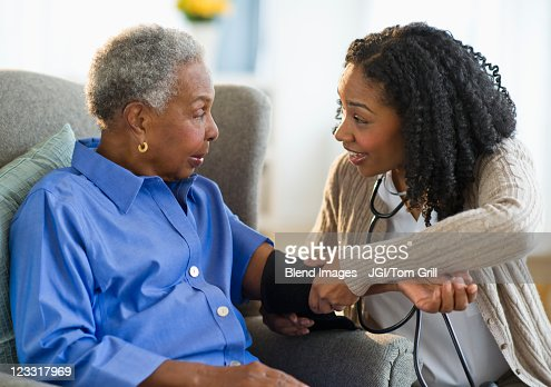 Nurse taking woman's blood pressure : Stock Photo