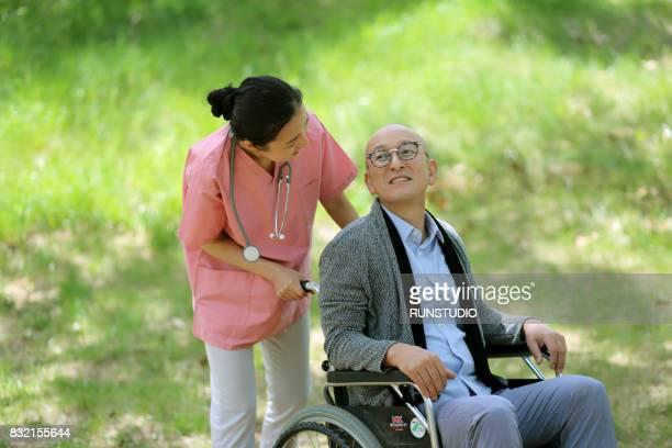 nurse talking to an old man sitting in a wheelchair