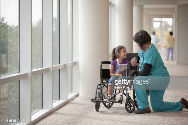 Nurse talking to girl in wheelchair