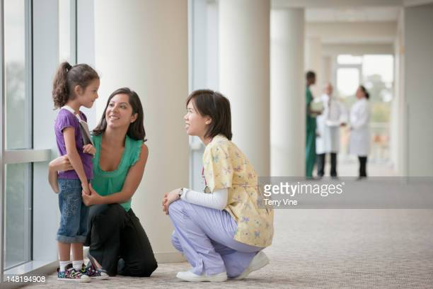 Nurse talking to mother and daughter in corridor