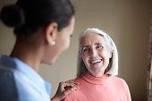 Nurse talking to older woman in home