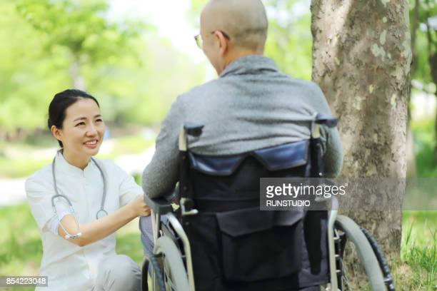 Nurse talking to senior man in wheelchair
