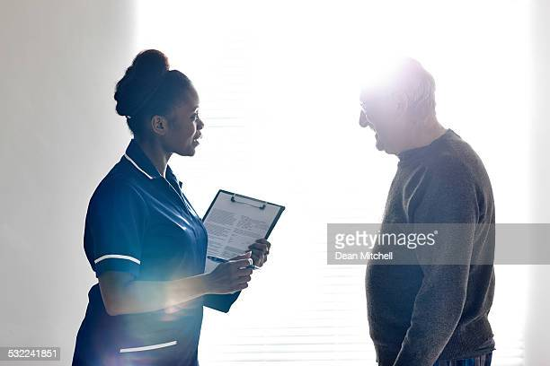 Nurse talking with senior patient at hospital