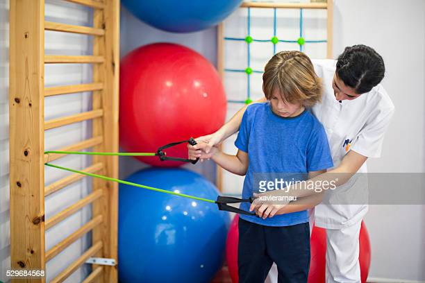 Nurse teaching boy how to exercise with elastic band