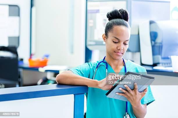 Personal de enfermería de actualización digital paciente gráficos en la moderna sala de emergencias