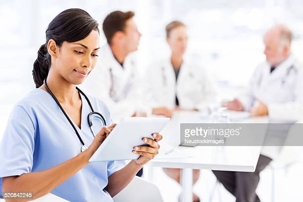 Nurse Using Digital Tablet With Medical Team Discussing In Boardroom