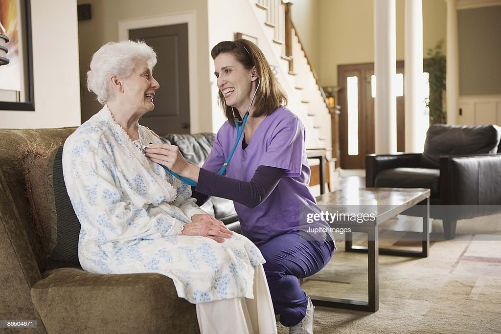 Nurse using stethoscope on patient at home : Stock Photo