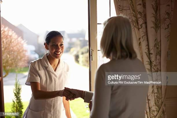 Nurse visiting older woman at home