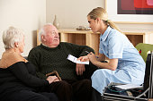 A female nurse visits an older couple at their home.  The nurse is wearing light blue scrubs with white trim and is holding pen and piece of paper.  There are wooden shelves behind the three and there