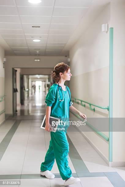 Krankenschwester zu Fuß in einem Krankenhaus-Korridor