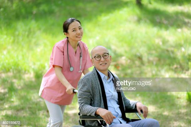 nurse walking in the park with an old man sitting in a wheelchair
