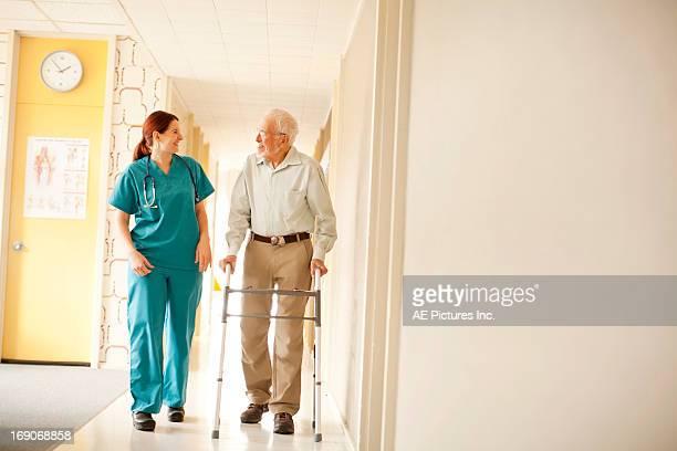 Nurse walking with man using walker