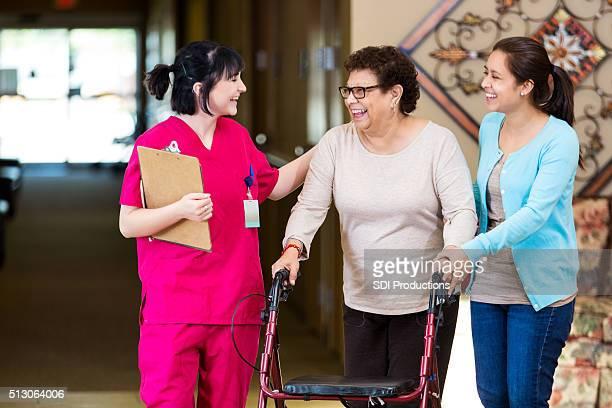Nurse walks with senior woman in nursing home