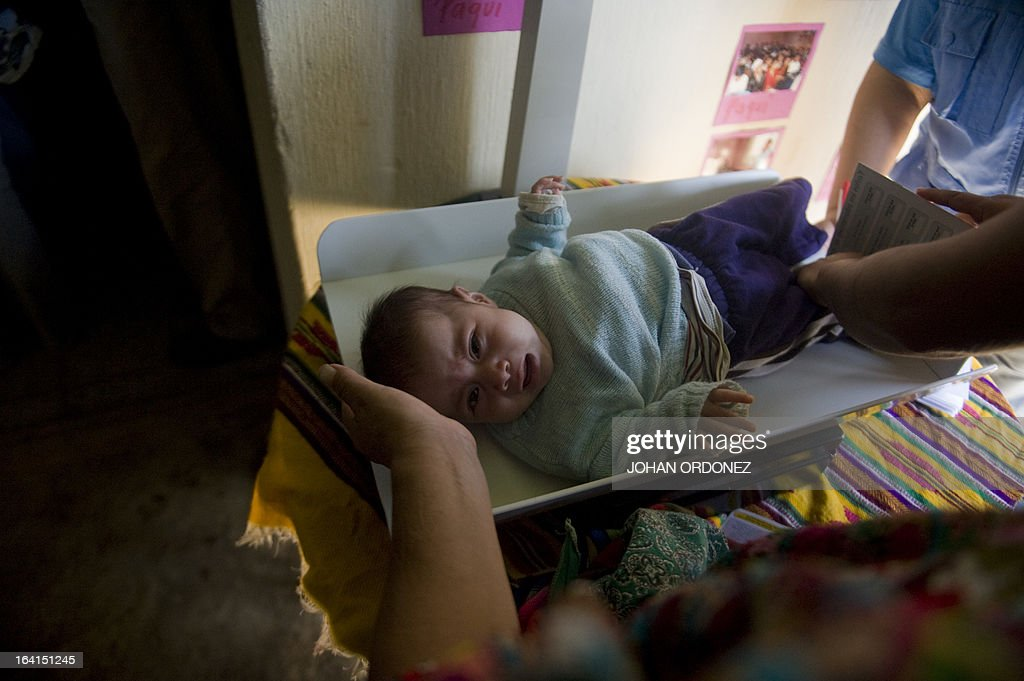 A nurse weighs a baby in a community home during visit of Tony Lake Executive Director of the United Nations Children's Fund during a visit to the...
