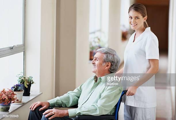 Krankenschwester mit alter Mann im Rollstuhl Blick durchs Fenster