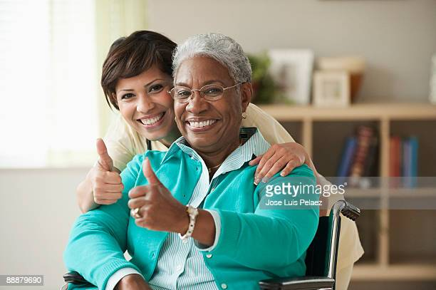 Nurse with elderly female patient giving thumbs up