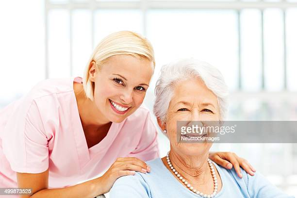 Nurse With Hands On Senior Patient's Shoulders In Nursing Home