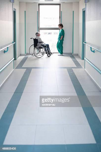 Infirmière avec le patient en fauteuil roulant de parler d'une