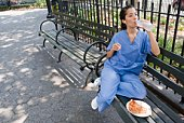 Nurse with pizza and bottled water on park bench