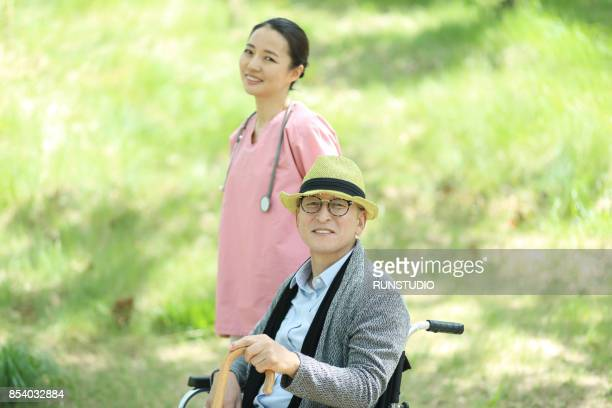 Nurse with wheeling patient outdoors
