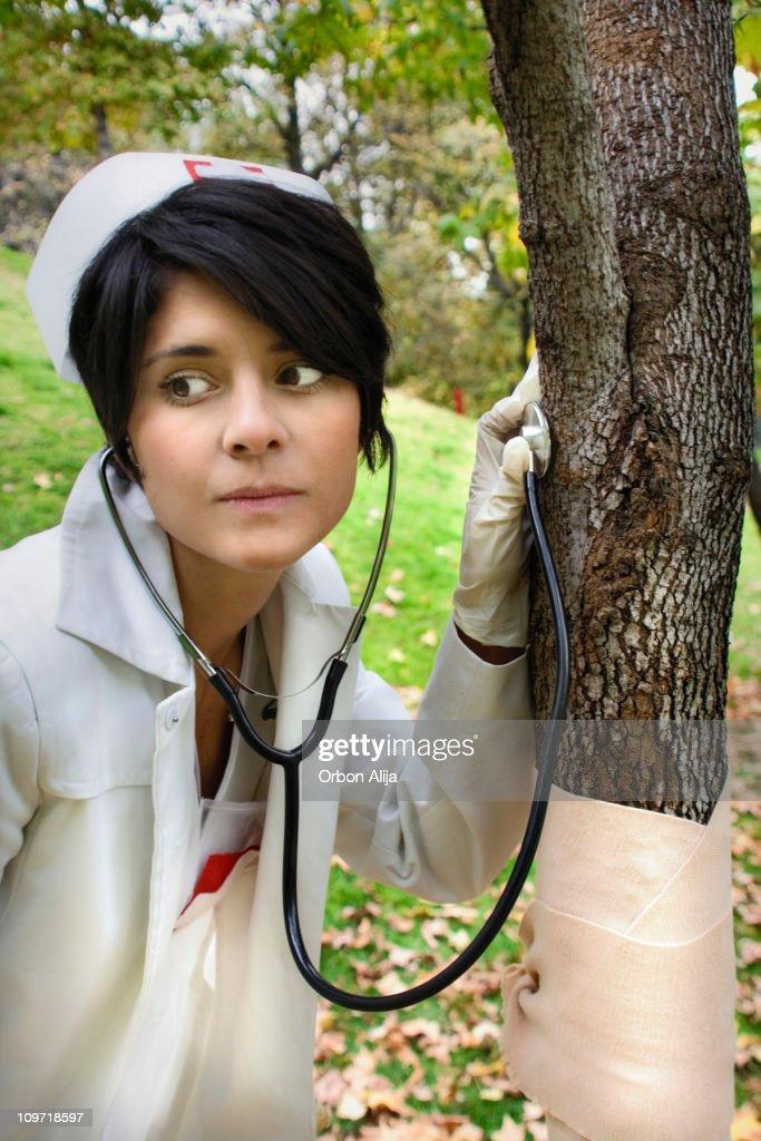 Nurse Woman Checking Bandaged Tree with Stethoscope : Stock Photo