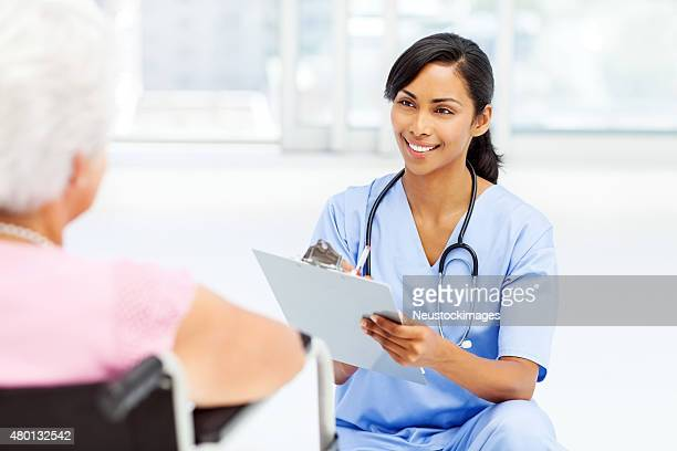 Nurse Writing Notes On Clipboard While Looking At Senior Patient