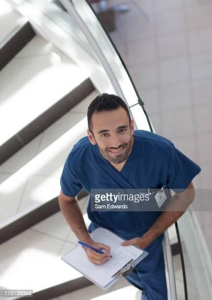 Krankenschwester Schreiben in Zwischenablage auf der Treppe