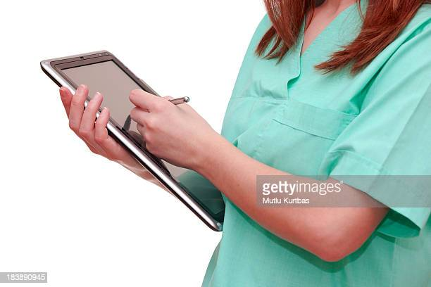 Nurse writing on tablet in green uniform