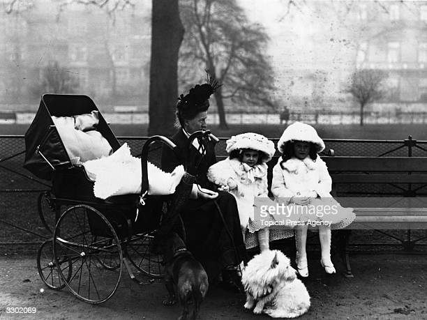 A nursemaid sits with her two young charges who are dressed in pale furtrimmed coats hats and gloves next to a pram and two dogs in Hyde Park London
