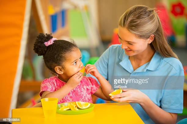Nursery Teacher and Child Eating Oranges