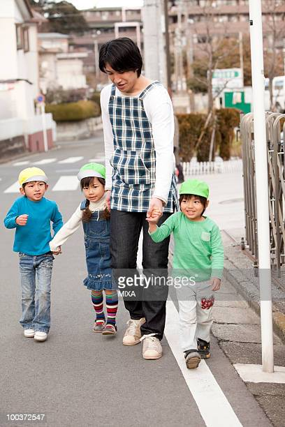Nursery Teacher and Children Walking