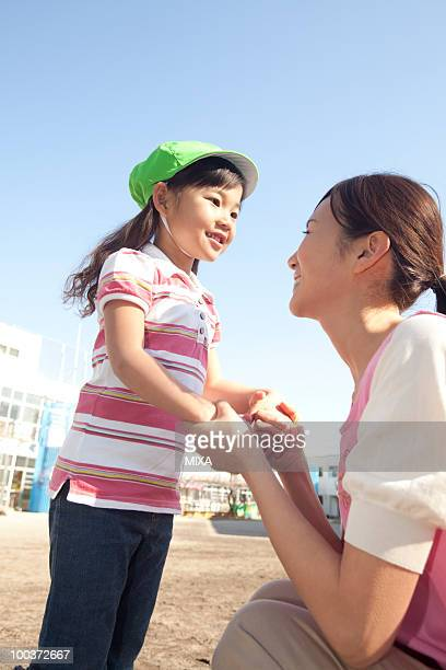 Nursery Teacher and Girl Playing
