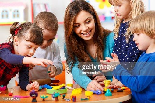 Nursery insegnante giocando con i bambini