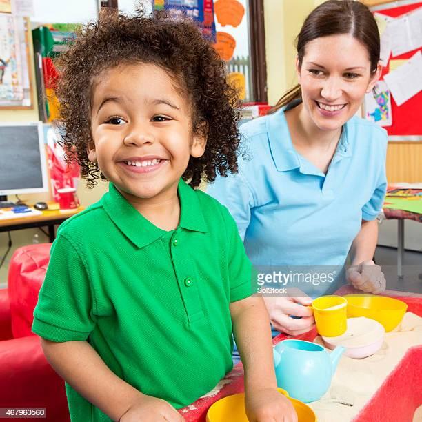 Kinderzimmer Arbeiter mit kleinen Jungen spielen im Sandkasten