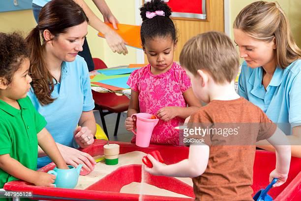 Kindergarten Arbeitnehmer mit Kindern spielen im Sandkasten