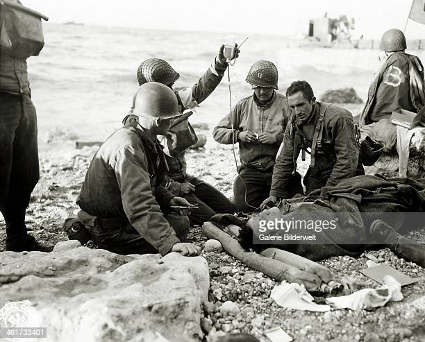 Nurses administer a plasma transfusion to a wounded survivor of a landing craft at 'Fox Green' sector portion of Omaha Beach 6th June 1944 The...