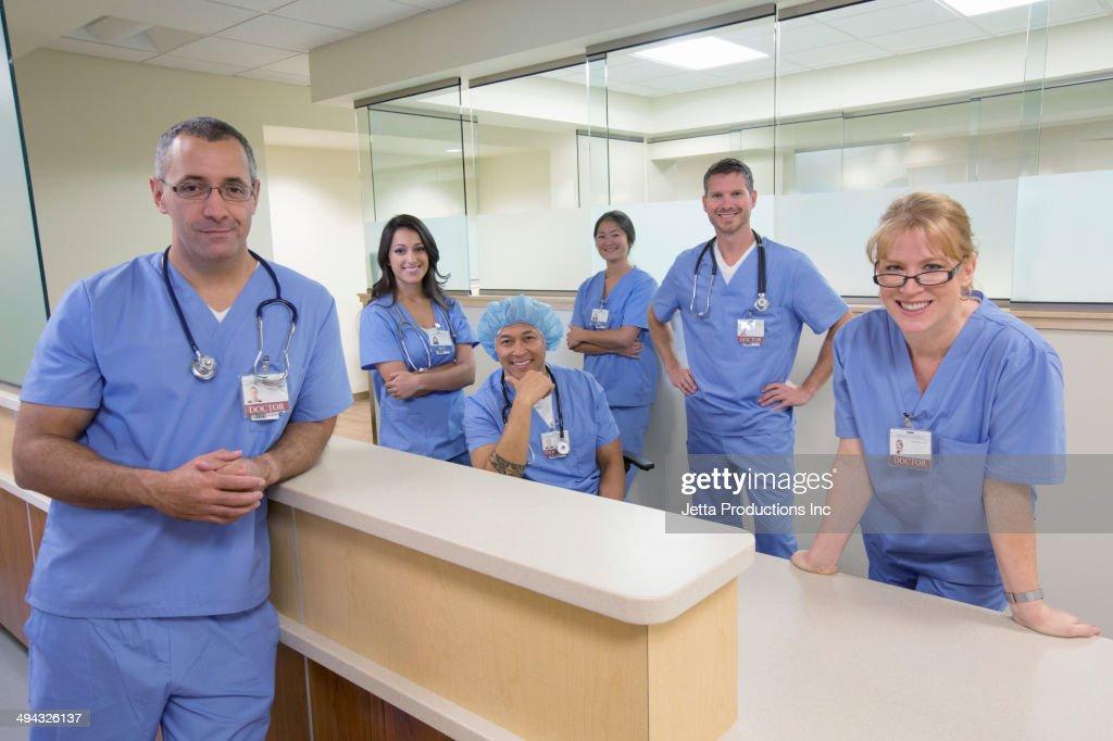 Nurses and doctors smiling at nurses station