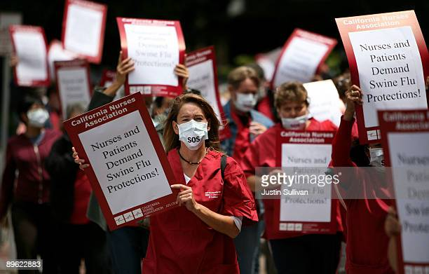 Nurses and hospital workers carry signs and wear masks as they protest outside of the University of California San Francisco medical center August 5...