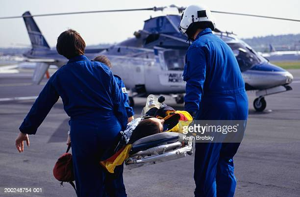 Nurses and pilot carrying patient on stretcher to helicopter