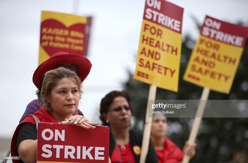 Nurses carry signs as they strike outside of Kaiser Permanente hospital on November 11 2014 in San Francisco California Nearly 18000 Kaiser...