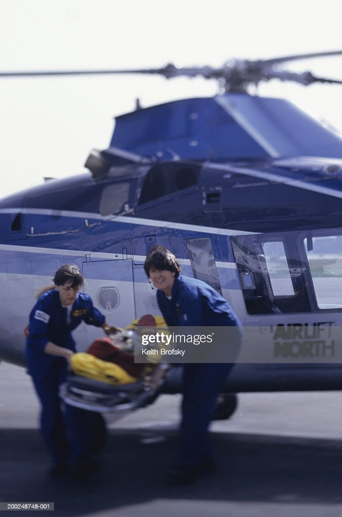 Nurses carrying patient on stretcher from helicopter