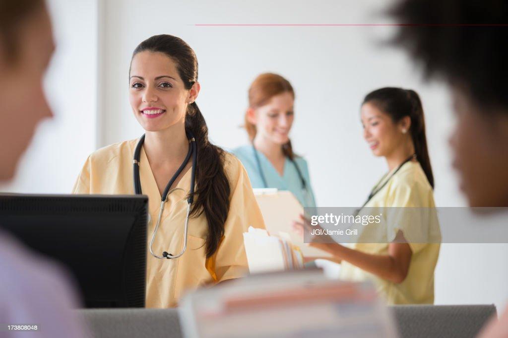 Nurses in colorful scrubs talking in hospital : Stock Photo