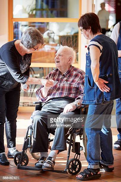 Nurses with smiling senior man in care home