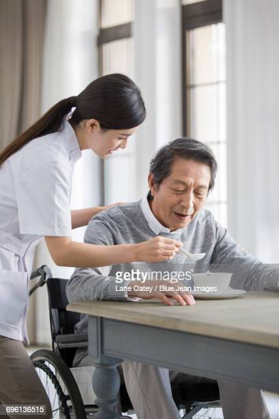Nursing assistant taking care of senior man in wheel chair